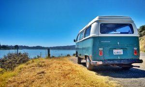 Blauwe Volkswagen camper bij een meer